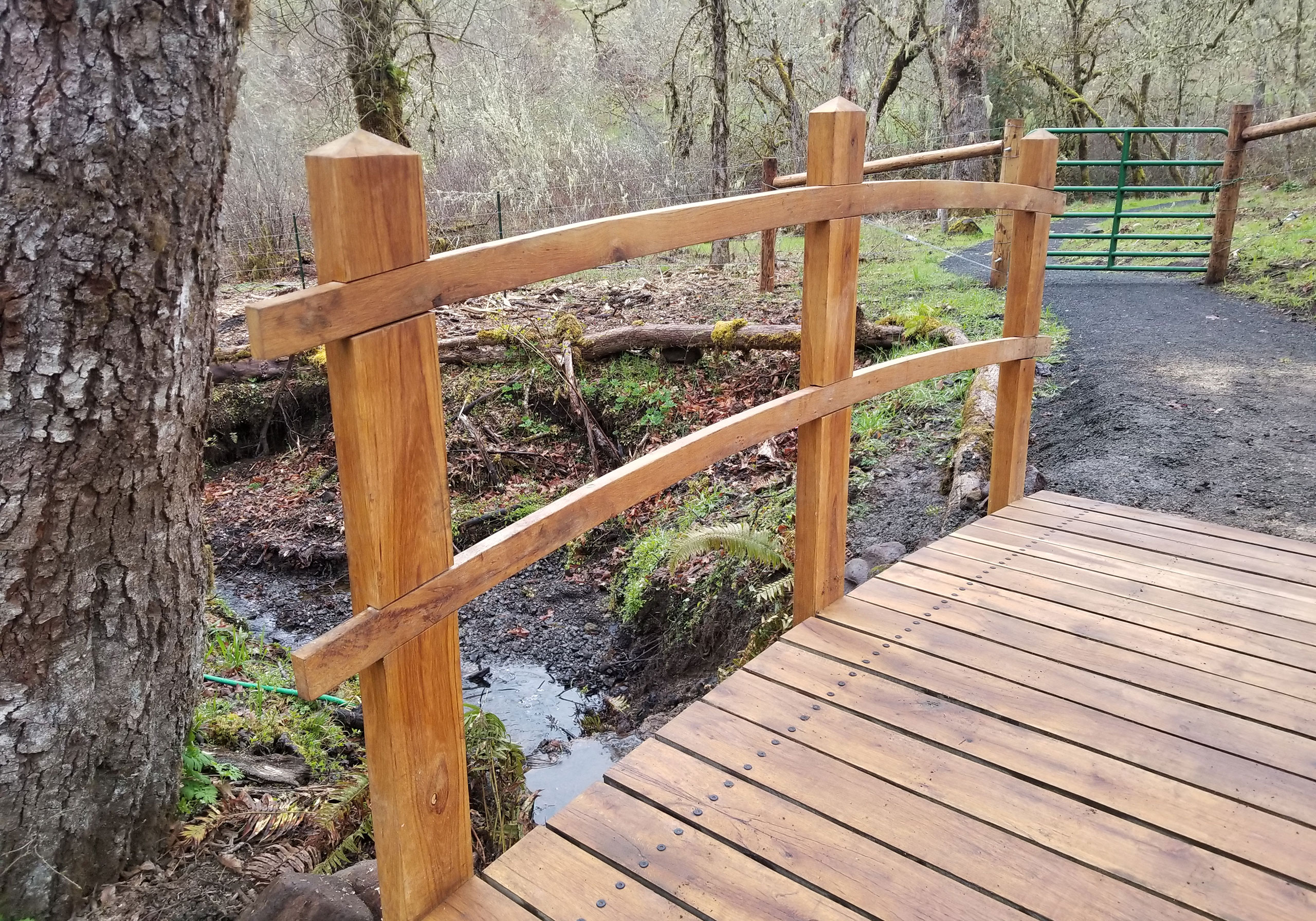 Finished oak arched bridge with inlaid arched railings on Bridge Trail at Crestmont Land Trust